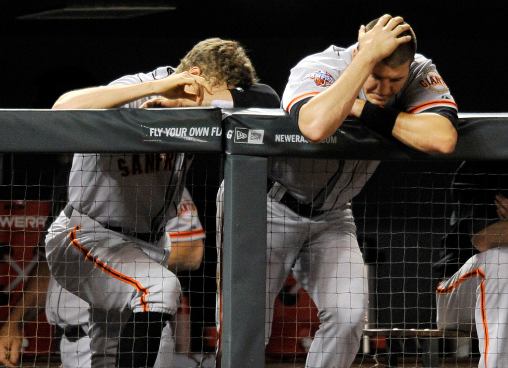. San Francisco Giants\' Hunter Pence, left, and Brett Pill react during the ninth inning of a baseball game against the Colorado Rockies on Friday, May 17, 2013, in Denver. Colorado defeated San Francisco 10-9. (AP Photo/Jack Dempsey)