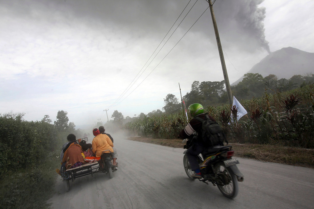 . Villagers flee on a volcanic ash-covered road as Mount Sinabung erupts in Karo, North Sumatra, Indonesia, Tuesday, Sept. 17, 2013. Thousands of people were evacuated from their villages following the eruption of the 2,600-meter (8,530-feet) volcano Sunday after being dormant for three years, sending thick ash into the sky with small rocks pelting neighboring villages.   (AP Photo/Binsar Bakkara)