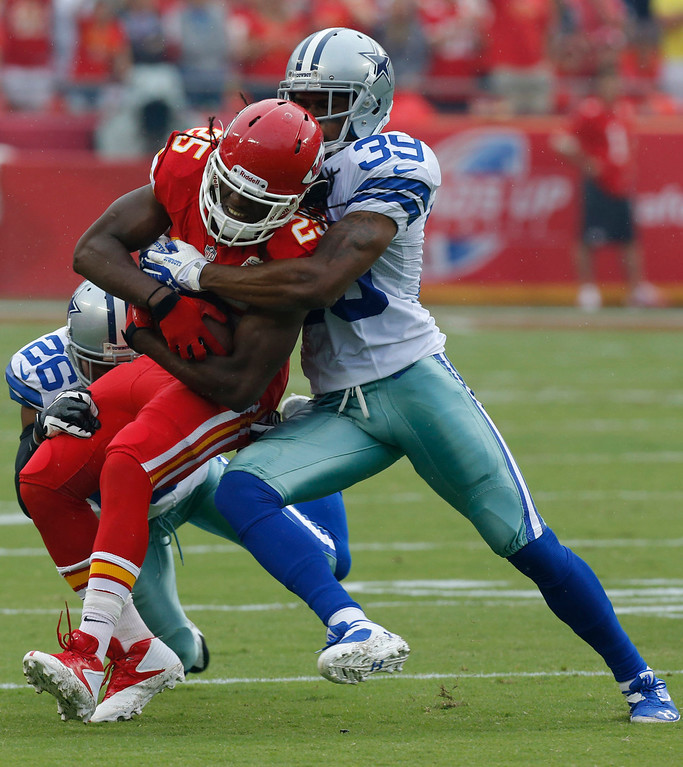 . Kansas City Chiefs running back Jamaal Charles (25) is tackled Dallas Cowboys strong safety Will Allen (26) and cornerback Brandon Carr (39) during the first half of an NFL football game at Arrowhead Stadium in Kansas City, Mo., Sunday, Sept. 15, 2013. (AP Photo/Ed Zurga)
