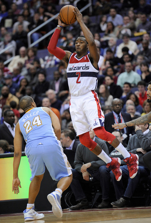 . Washington Wizards guard John Wall (2) passes the ball against Denver Nuggets guard Andre Miller (24) during the second half of an NBA basketball game, Friday, Feb. 22, 2013, in Washington. The Wizards won 119-113. (AP Photo/Nick Wass)