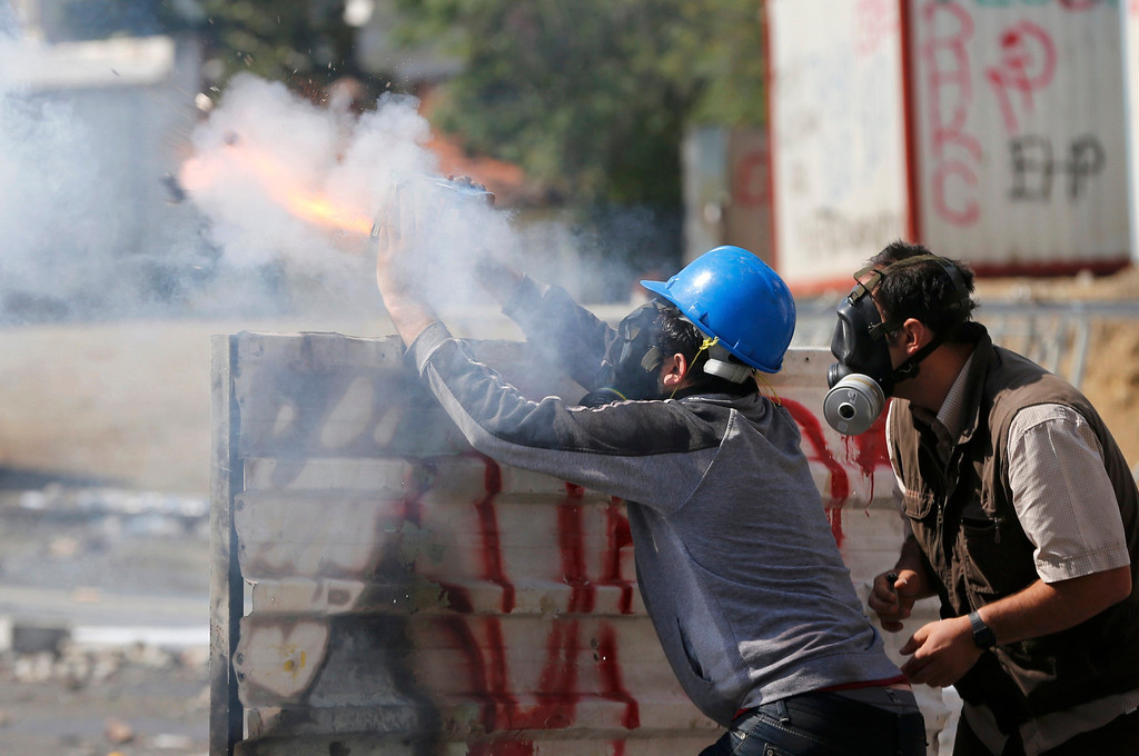 . A protester fires fireworks against riot police using a home made device during a protest at Taksim Square in Istanbul June 11, 2013.    REUTERS/Murad Sezer