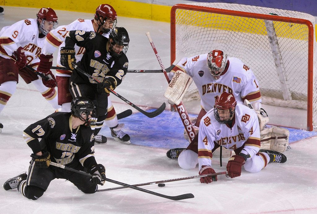 . DENVER, CO. - NOVEMBER 16: Western Michigan wing Justin Kovacs (17) tried to backhand a shot from his knees in the final period. Denver defenseman Josiah Didier (4) stopped his effort. The University of Denver hockey team defeated Western Michigan 1-0 at Magness Arena Saturday night, November 16, 2013.  Photo By Karl Gehring/The Denver Post