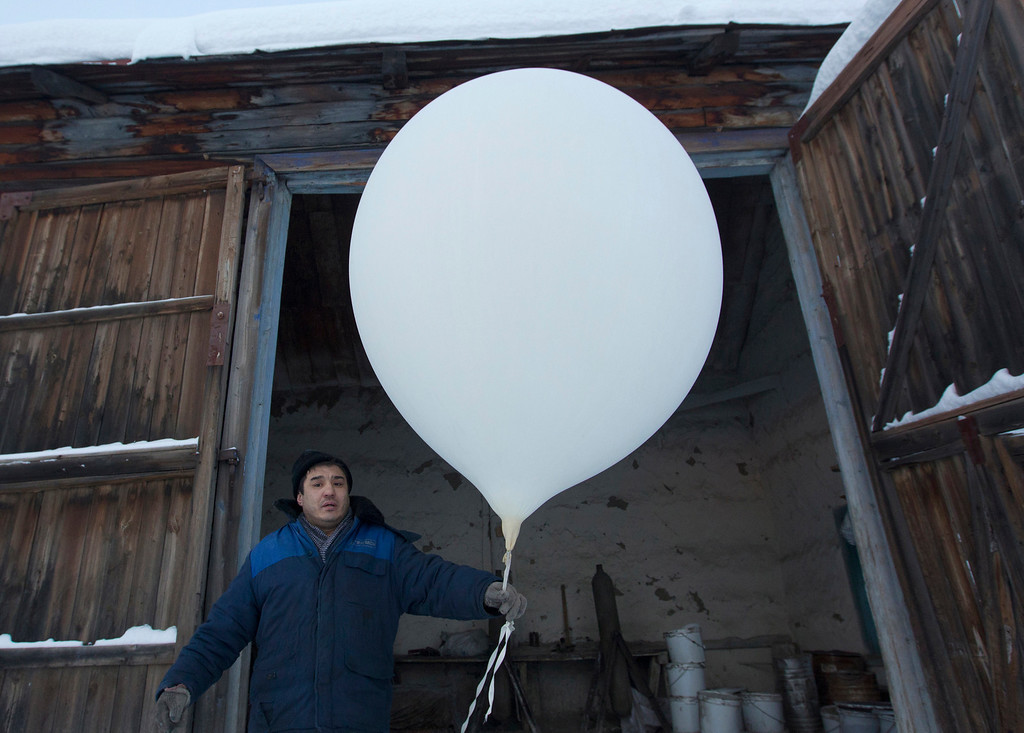 . Sergei Burtsev, 41, a meteorologist, prepares to launch a weather balloon in the village of Tomtor in the Oymyakon valley, in the Republic of Sakha, northeast Russia, January 30, 2013. The coldest temperatures in the northern hemisphere have been recorded in Sakha, the location of the Oymyakon valley, where according to the United Kingdom Met Office a temperature of -67.8 degrees Celsius (-90 degrees Fahrenheit) was registered in 1933 - the coldest on record in the northern hemisphere since the beginning of the 20th century. Yet despite the harsh climate, people live in the valley, and the area is equipped with schools, a post office, a bank, and even an airport runway (albeit open only in the summer). Picture taken January 30, 2013. REUTERS/Maxim Shemetov