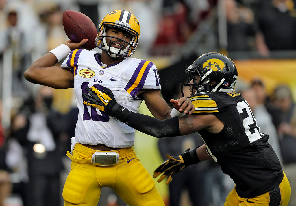 . LSU quarterback Anthony Jennings (10) throws a pass as he gets hit by Iowa linebacker Christian Kirksey (20) during the first quarter of the Outback Bowl NCAA college football game Wednesday, Jan. 1, 2014, in Tampa, Fla. (AP Photo/Chris O\'Meara)