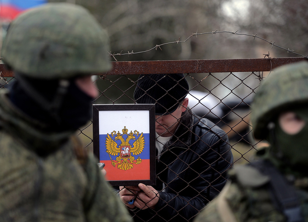 . The Russian coat of arms is placed on the gate as Russian soldiers stand guard after they took contol of the Ukrainian navy south headquarters base in Novoozerne on March 19, 2014. Russian forces seized control of a second Ukrainian navy base in western Crimea on Wednesday, AFP reporters saw, hours after capturing the main navy headquarters in Sevastopol. Some 50 Ukrainian servicemen were seen filing out of the base at Novoozerne as Russian soldiers stood by, while pro-Moscow militants raised the Russian flag over the base.  AFP PHOTO/ Filippo  MONTEFORTE/AFP/Getty Images