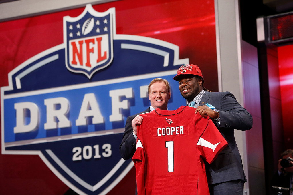 . Jonathan Cooper, from North Carolina, stands with NFL Commissioner Roger Goodell after being selected seventh overall by the Arizona Cardinals in the first round of the NFL football draft, Thursday, April 25, 2013, at Radio City Music Hall in New York. (AP Photo/Jason DeCrow)