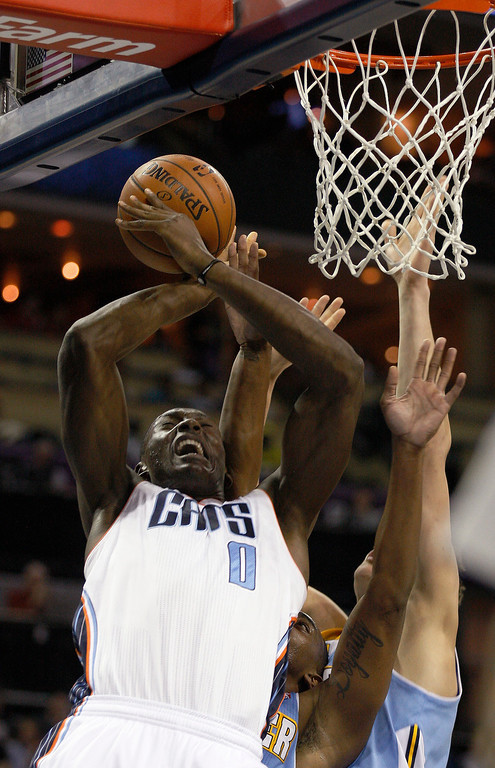 . Charlotte Bobcats center Bismack Biyombo (0) fights for a rebound against the Denver Nuggets in the first half of an NBA basketball game in Charlotte, N.C., Monday, March 10, 2014. (AP Photo/Nell Redmond)