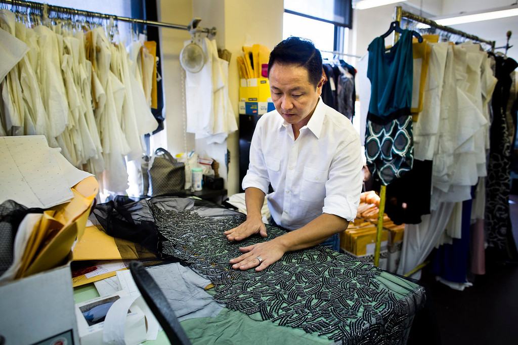 . Creative Director Il Park handles fabric in the workspace of fashion designer Carmen Marc Valvo\'s New York studio. Valvo will show his Spring 2014 show on Sept. 6 at Lincoln Center in New York. (AP Photo/John Minchillo)