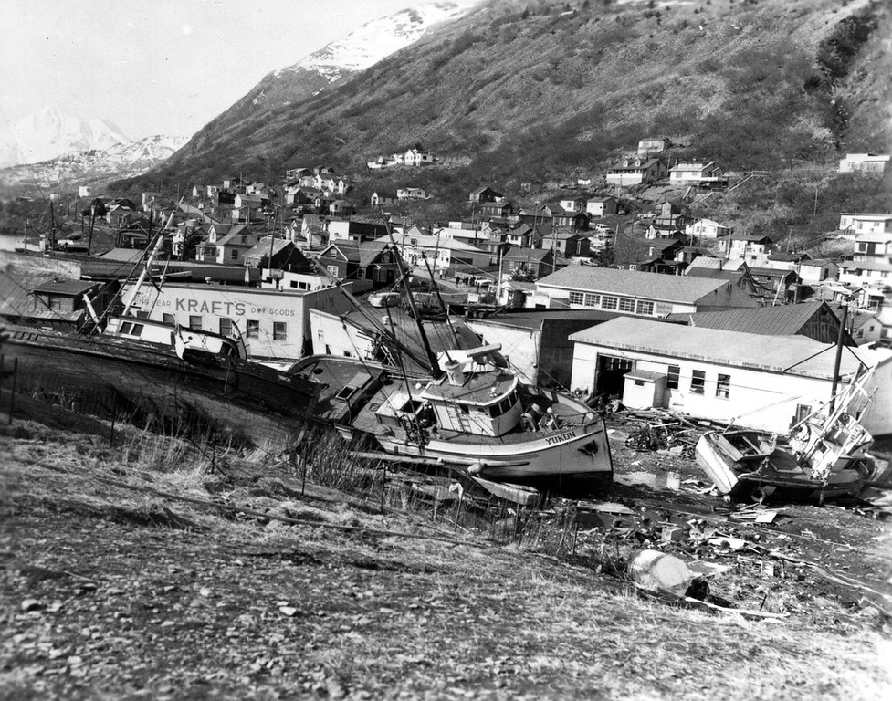 . Alaska Earthquake March 27, 1964. Chaotic condition of the commercial section of the city of Kodiak following inundation by seismic sea waves. The small- boat harbor, which was in left background, contained an estimated 160 crab and salmon fishing boats when the waves struck. Tsunamis washed many vessels into the heart of Kodiak. Photo by U.S. Navy, March 30, 1964, U.S. Geological Survey