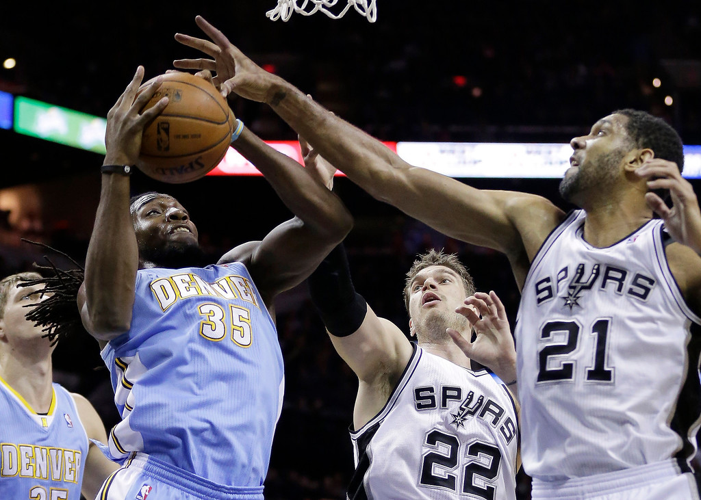 . Denver Nuggets\' Kenneth Faried (35) grabs a rebound against San Antonio Spurs\'  Tiago Splitter (22) and Tim Duncan (21) for a rebound during the first half of an NBA basketball game, Wednesday, March 26, 2014, in San Antonio. (AP Photo/Eric Gay)