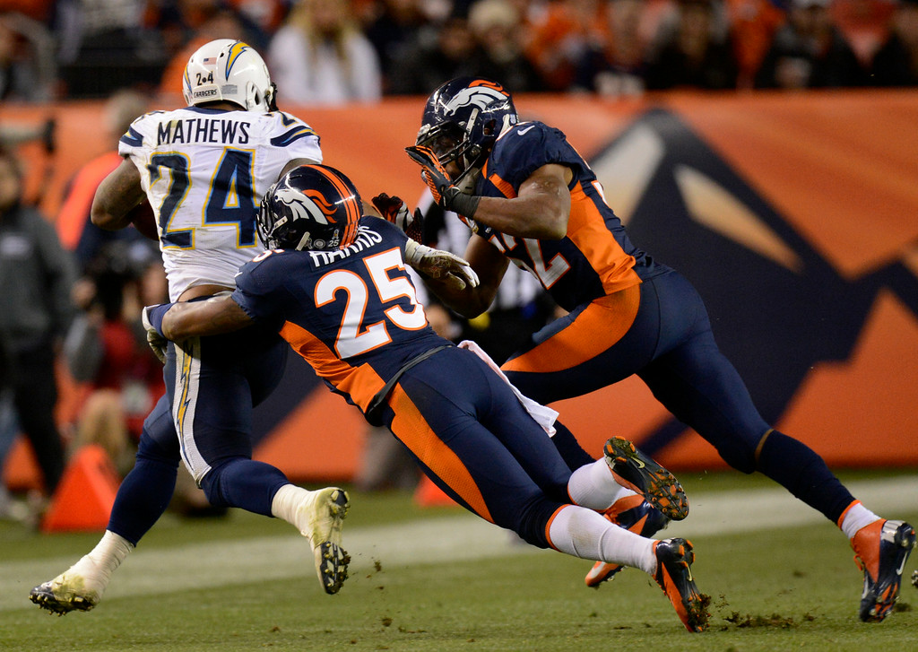 . Chargers running back Ryan Mathews tries to escape a tackle by Chris Harris and Tony Carter of the Broncos. (Joe Amon, The Denver Post)
