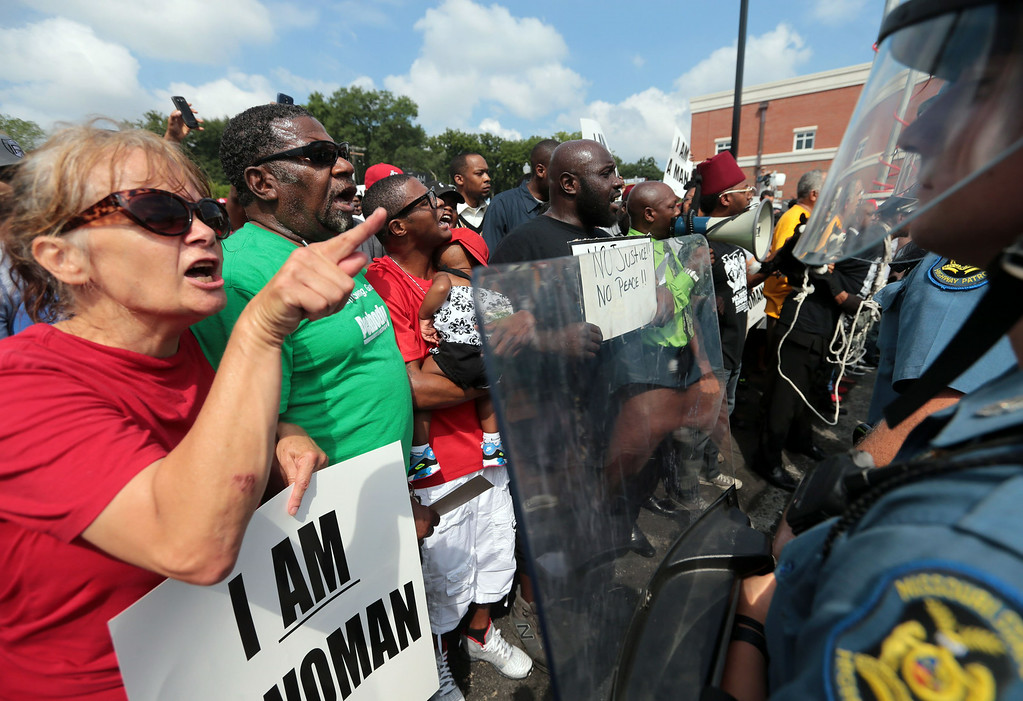 ". ""This is an shooting of an 18-year boy who was supposed to start school today,\"" said protestor Fiona Wilson of Ferguson , who shouts at the barricade of Missouri State Highway Patrol troopers in front of the Ferguson police station on Monday, Aug. 11, 2014. \""I don\'t want this to be appear as a racial thing. It\'s a police brutality issue. The officer used excessive force. It\'s not a black and white thing. That\'s why I am out here. I want more white people to come out,\"" said Wilson. Marchers are entering a third day of protests against Saturday\'s police shooting of Michael Brown.  (AP Photo/St. Louis Post-Dispatch, Laurie Skrivan)"