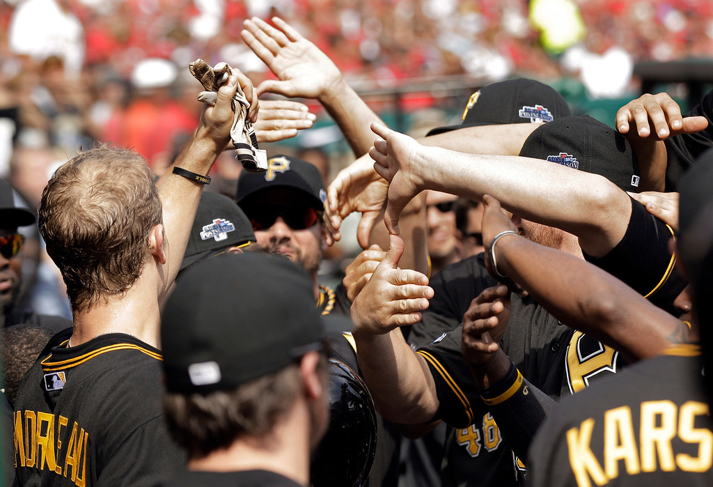 . Pittsburgh Pirates\' Justin Morneau, left, is congratulated after scoring against the St. Louis Cardinals in the fifth inning of Game 2 of baseball\'s National League division series on Friday, Oct. 4, 2013, in St. Louis. The Pirates won 7-1. (AP Photo/Charlie Riedel)