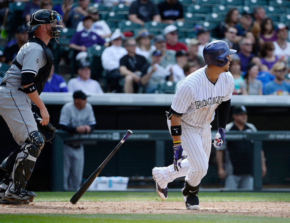 . Colorado Rockies outfielder, Carlos Gonzalez, hits a double, scoring Charlie Blackmon, and Michael Cuddyer,  in the 8th inning against the Tyler Flowers, left, and Chicago White Sox at Coors Field Wednesday afternoon, April 09, 2014. The Rockies went on to win 10-4. (Photo By Andy Cross / The Denver Post)