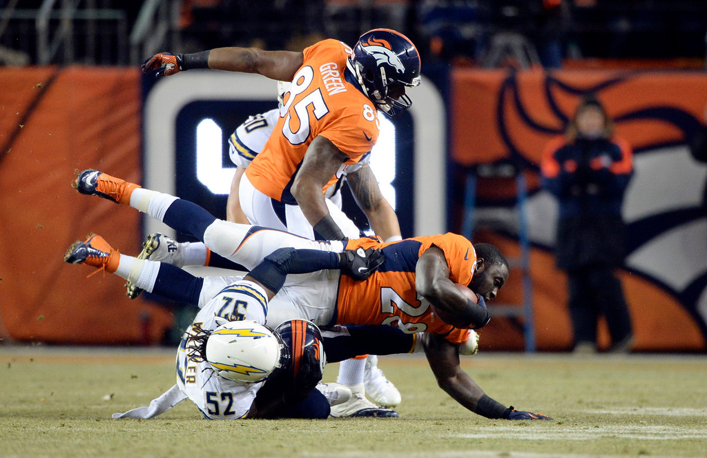 . Denver Broncos running back Montee Ball (28) gets his helmet ripped off by San Diego Chargers inside linebacker Reggie Walker (52) during the first half.  The Denver Broncos vs. the San Diego Chargers at Sports Authority Field at Mile High in Denver on December 12, 2013. (Photo by Hyoung Chang/The Denver Post)