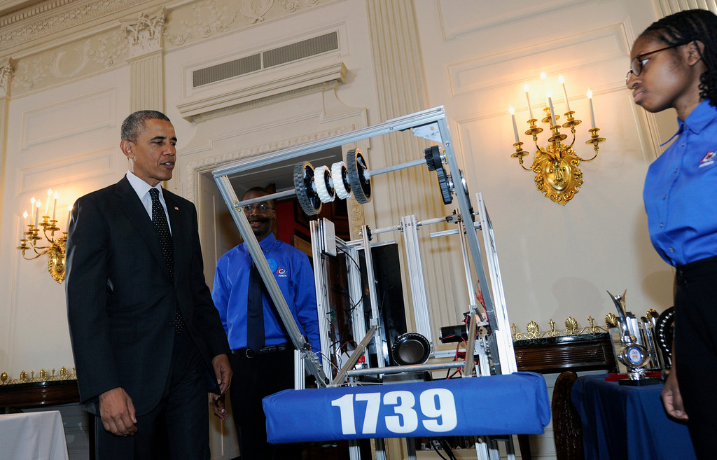 . President Barack Obama stands with John Moore, 19, center, and Lydia Wolfe, 18, right, both of Chicago, as he looks over a robot during a tour of the 2014 White House Science Fair exhibits that are on display in the State Dining Room at the White House in Washington, Tuesday, May 27, 2014.  (AP Photo/Susan Walsh)