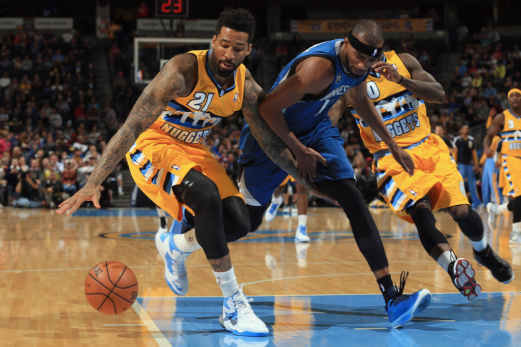 . DENVER, CO - NOVEMBER 15:  Wilson Chandler #21 of the Denver Nuggets grabs a loose ball away from Corey Brewer #13 of the Minnesota Timberwolves at Pepsi Center on November 15, 2013 in Denver, Colorado. (Photo by Doug Pensinger/Getty Images)