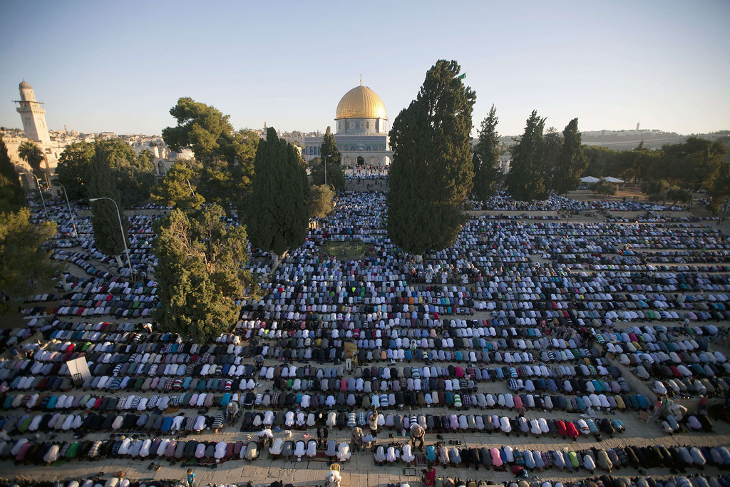 . Palestinian Muslim men perform the morning Eid Al-Fitr prayer in front of the Dome of Rock at the Al-Aqsa Mosque compound, Islam\'s third most holy site, in the old city of Jerusalem on August 8, 2013, marking the end of the fasting month of Ramadan. AHMAD GHARABLI/AFP/Getty Images