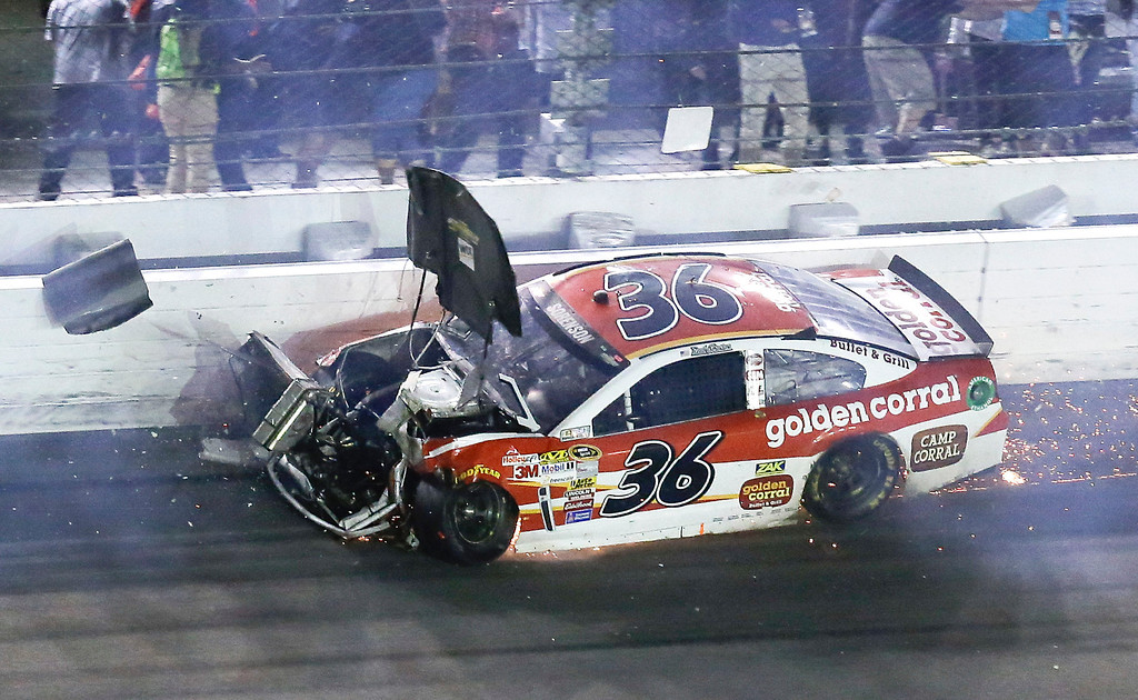 . The hood flies off of Reed Sorenson\'s car after he was involved in a crash on the last lap of the Daytona 500 NASCAR Sprint Cup Series auto race at Daytona International Speedway in Daytona Beach, Fla., Sunday, Feb. 23, 2014. (AP Photo/John Raoux)