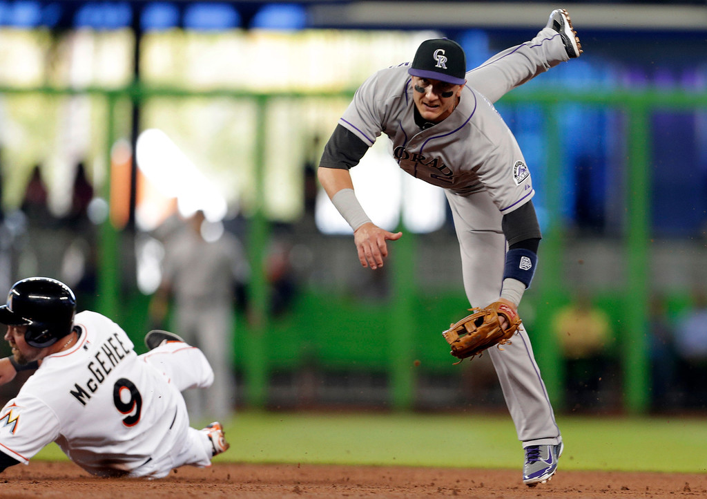 . Colorado Rockies shortstop Troy Tulowitzki, right, watches his throw to first base after forcing out Miami Marlins\' Casey McGehee (9) out at second base during the first inning of a baseball game, Thursday, April 3, 2014, in Miami. The Marlins\' Garrett Jones was out a first for a double play. (AP Photo/Lynne Sladky)