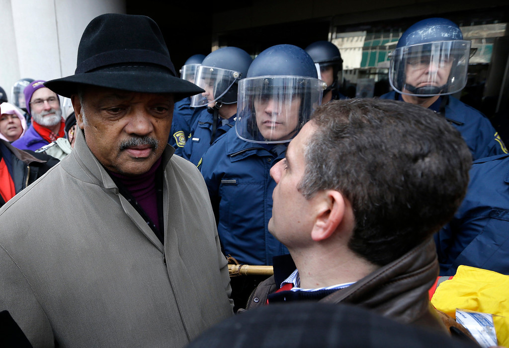 . Rev. Jesse Jackson, left, and Lansing Mayor Virg Bernero, right, try to enter past Michigan State Police at the George W. Romney State Building, where Gov. Snyder has an office in Lansing, Mich., Tuesday, Dec. 11, 2012. The crowd is protesting right-to-work legislation passed last week. Michigan could become the 24th state with a right-to-work law next week. Rules required a five-day wait before the House and Senate vote on each other\'s bills; lawmakers are scheduled to reconvene Tuesday and Gov. Snyder has pledged to sign the bills into law. (AP Photo/Paul Sancya)