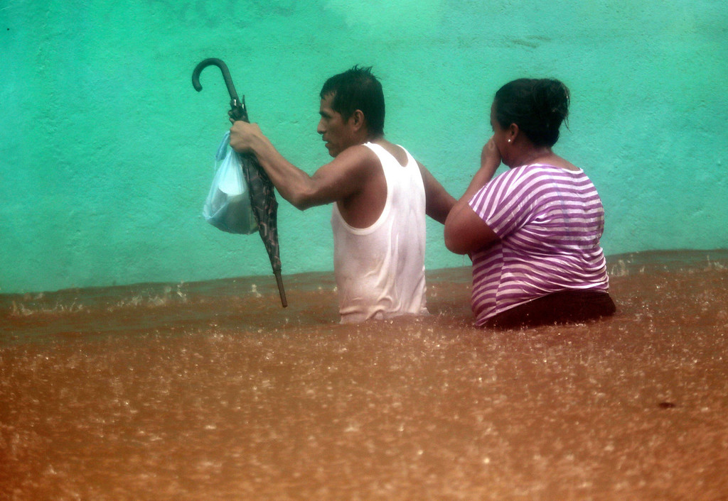 . TOPSHOTS A couple wades in a flooded street in Acapulco, Guerrero state, Mexico following tropical storm Manuel which landed in the Pacifiic coast of Mexico on September 15, 2013. Hurricane Ingrid and Tropical Storm Manuel triggered rain, landslides and floods on Mexico\'s east and west coasts Sunday, killing at least 20 people and forcing thousands to evacuate before landfall. Manuel was weakening after making landfall near the Colima state town of Manzanillo, packing top winds of almost 50 miles (85 kilometers) per hour as it moved northwest, the US hurricane center said.   Pedro PARDO/AFP/Getty Images