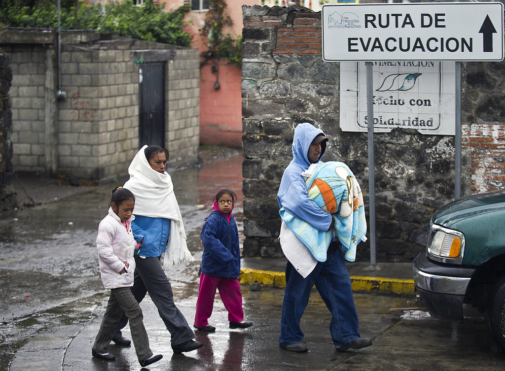 . A family walks in Santiago Xalitzintla community near Popocatepetl volcano, in Puebla, Mexico, on May 13, 2013. According to a report by the National Center of Prevention of Disasters (CENAPRED) the yellow alert phase three is still in force. Ronaldo Schemidt/AFP/Getty Images
