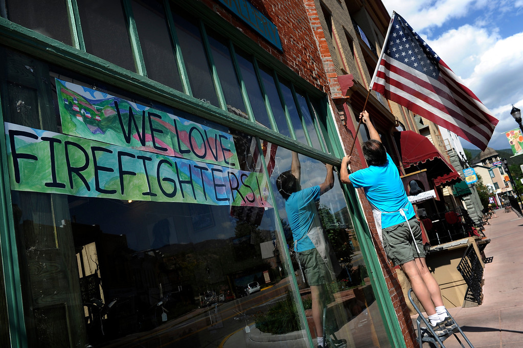 """. Ken Riesterer, of the Green Horse Gallery, fixes the flag outside his shop on Manitou Ave in Manitou Springs, CO, Friday, July 06, 2012. He said he is concerned his business will suffer from the impact the Waldo Canyon Fire might have on tourism. He said, \""""We\'re concerned about the people canceling their reservations at the bed and breakfasts. They\'re usually the art buyers.\"""" Craig F. Walker, The Denver Post"""