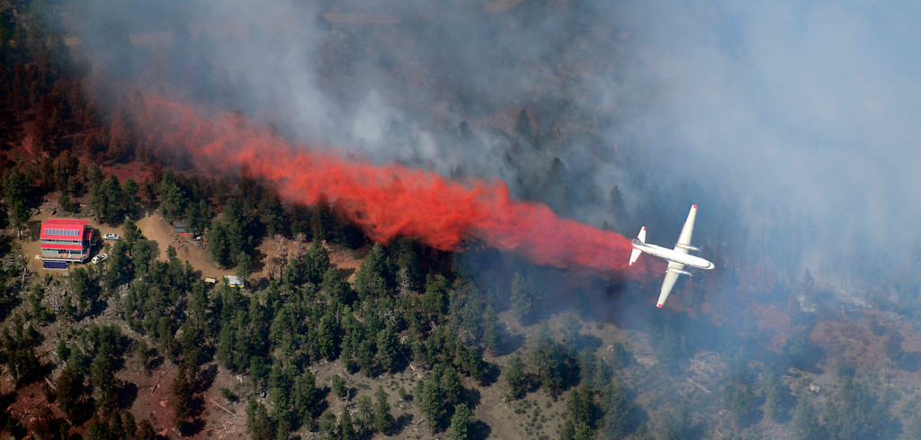 . Seen from a helicopter, a slurry bomber makes a drop in an attempt to protect a house and the ridge line during the High Park Fire west of Fort Collins, CO. Eric Lutzens, The Denver Post