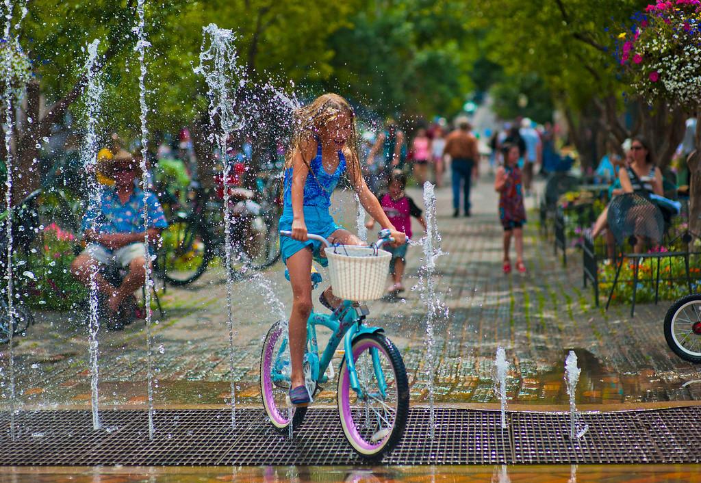 . Aspen, CO, U.S.A  Stephanie Freednash, 7, rides her bike through designer Nick DeWolf\'s famed dancing fountain on Aspen\'s Hyman Avenue mall.  Photo by Evan Semón,