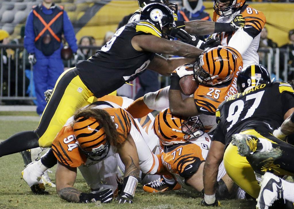 . Cincinnati Bengals running back Gio Bernard (25) gets hit by Pittsburgh Steelers defensive end Ziggy Hood, top left, as he scores a touchdown in the first half of an NFL football game in Pittsburgh, Sunday, Dec. 15, 2013. (AP Photo/Gene J. Puskar)
