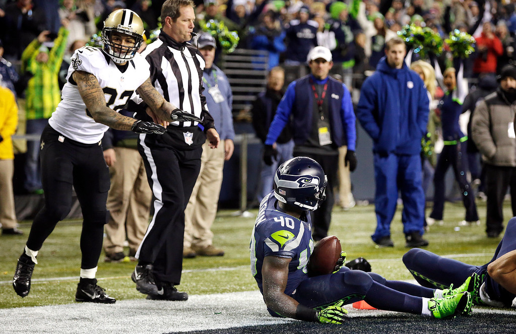 . New Orleans Saints\' Kenny Vaccaro, left, signals incomplete, but Seattle Seahawks\' Derrick Coleman\'s (40) possession of the football at right was ruled a touchdown in the second half of an NFL football game Monday, Dec. 2, 2013, in Seattle. (AP Photo/Scott Eklund)