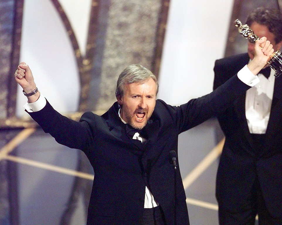 ". Director James Cameron raises his Oscar after winning in the Best Director Category during the 70th Academy Awards at Shrine Auditorium 23 March. Cameron won for his movie ""Titanic.\""  TIMOTHY A. CLARY/AFP/Getty Images"