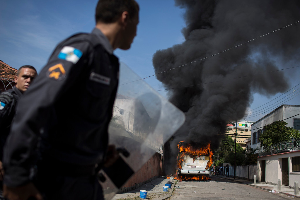 . Policemen patrol near a burning bus after it was set on fire near the area recently occupied by squatters in Rio de Janeiro, Brazil, Friday, April 11, 2014. Squatters in Rio de Janeiro are clashing with police after a Brazilian court ordered that 5,000 people be evicted from abandoned buildings of a telecommunications company. Officers have used tear gas and stun grenades to try to disperse the families. (AP Photo/Felipe Dana)