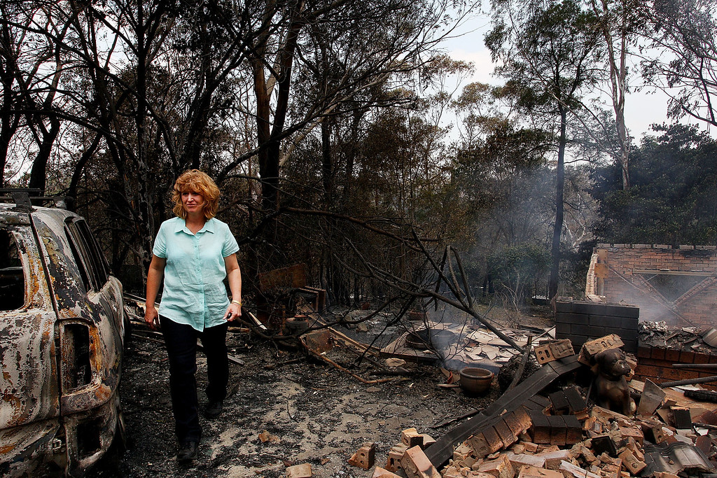 . Leanne Brown inspects the remains of her home following severe bush fires on October 18, 2013 in Winmalee, Australia. One man has died and dozens of properties have been destroyed in bush fires that are devastating the Blue Mountains and Central Coast regions of New South Wales.  (Photo by Lisa Maree Williams/Getty Images)