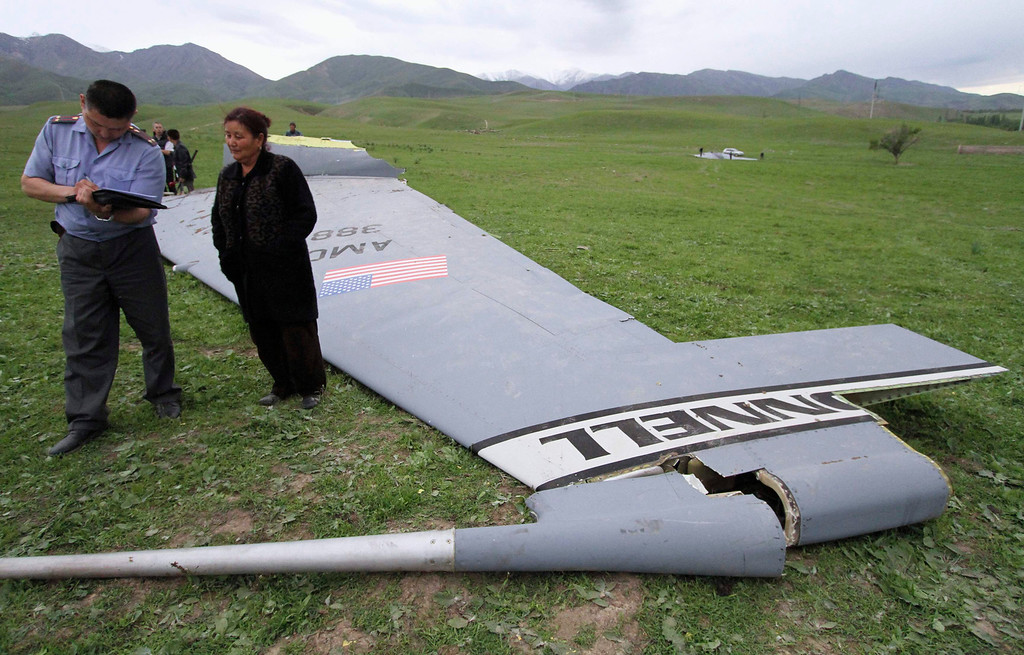 . An Interior Ministry officer questions local residents near the wreckage of the Boeing KC-135 Stratotanker plane near the site of its crash near the Kyrgyz village of Chaldovar, May 3, 2013. REUTERS/Vladimir Pirogov
