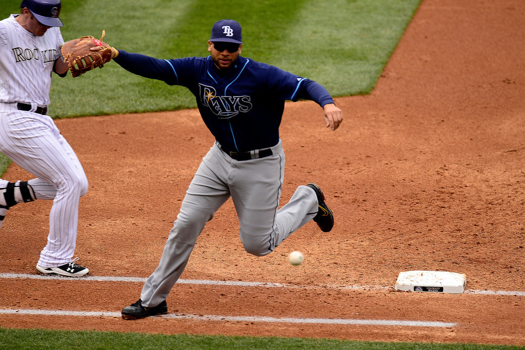 . DENVER, CO - MAY 5: James Loney (21) of the Tampa Bay Rays cannot wrangle an errant throw by Sean Rodriguez (1) as Josh Rutledge (14) of the Colorado Rockies makes it to first base safely during the Rockies\' 8-3 loss.   (Photo by AAron Ontiveroz/The Denver Post)