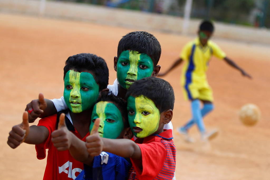 . Indian boys with faces painted in colors resembling those of the Brazil\'s flag pose for photographers, during a game of soccer in Bangalore, India, Tuesday, June 10, 2014. Soccer fans around the world are gearing up to watch the World Cup soccer tournament that kicks off Thursday in Brazil. (AP Photo/ Aijaz Rahi)
