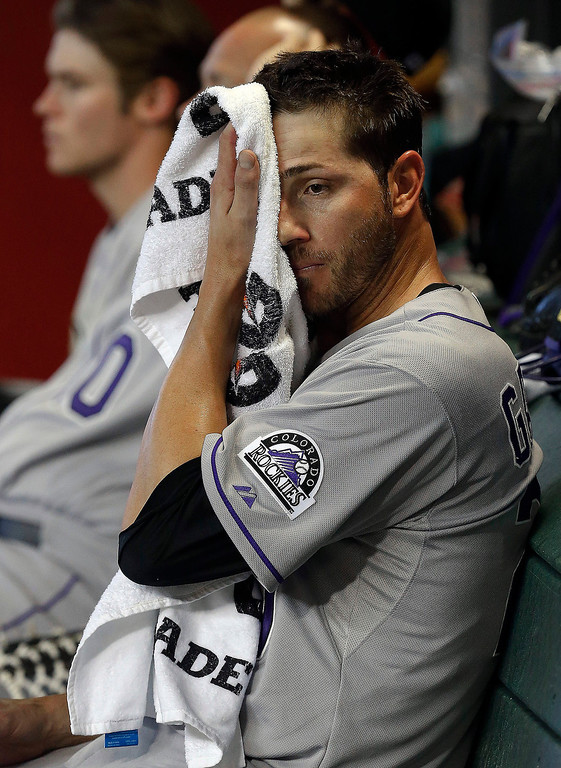 . Colorado Rockies\' Jon Garland wipes his face as he sits in the dugout during the fifth inning of a baseball game against the Arizona Diamondbacks, Sunday, April 28, 2013, in Phoenix. Garland got the loss as the Diamondbacks defeated the Rockies 4-2. (AP Photo/Ross D. Franklin)