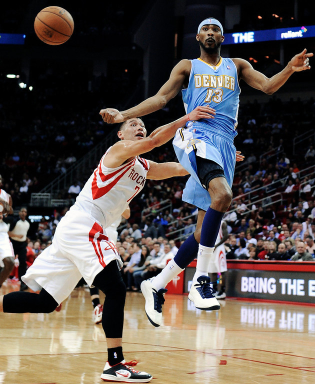 . Denver Nuggets\' Corey Brewer (13) passes off the ball under pressure from Houston Rockets\' Jeremy Lin (7) in the first half of an NBA basketball game Wednesday, Jan. 23, 2013, in Houston. (AP Photo/Pat Sullivan)