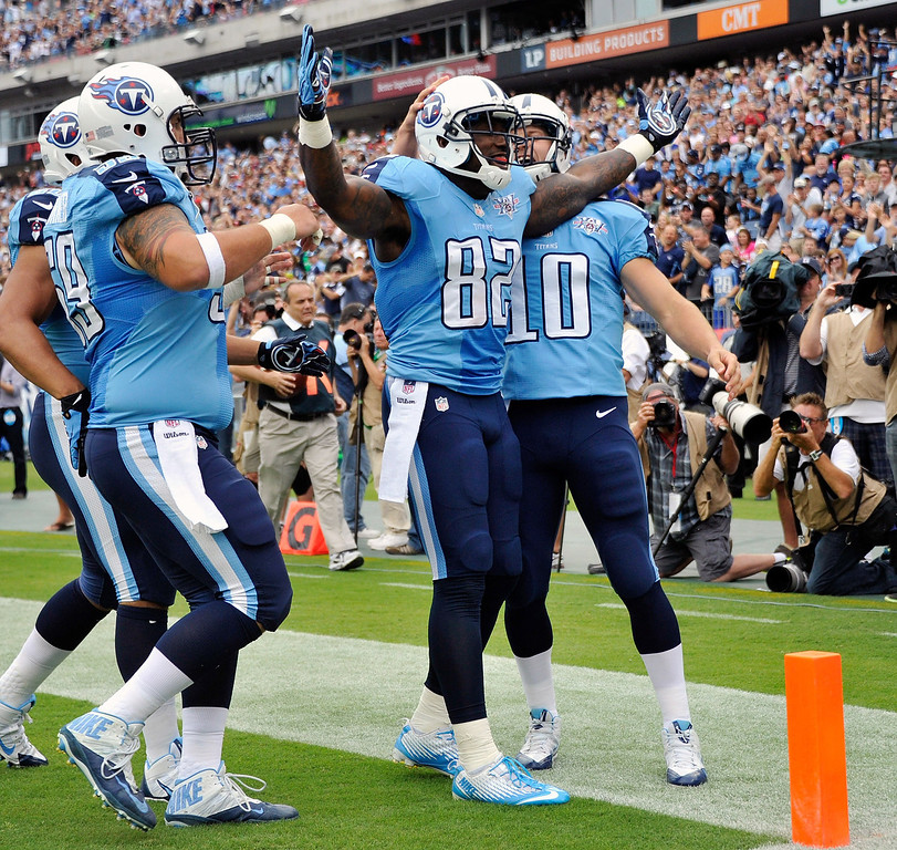 . NASHVILLE, TN - SEPTEMBER 29:  Tight end Delanie Walker #82 of the Tennessee Titans is congratulated by teammates after scoring a touchdown against the New York Jets at LP Field on September 29, 2013 in Nashville, Tennessee.  (Photo by Frederick Breedon/Getty Images)