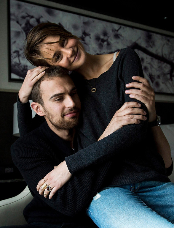 ". In this Thursday, March 6, 2014 file photo, actors Theo James, left, and Shailene Woodley pose for a photograph as they promote the movie ""Divergent,\"" in Toronto. The 22-year-old \""Divergent\"" star gives hearty embraces often more than one - to everyone she meets. Woodley and James star in the anticipated first film in the young adult trilogy by author Veronica Roth. (AP Photo/The Canadian Press, Nathan Denette, file)"