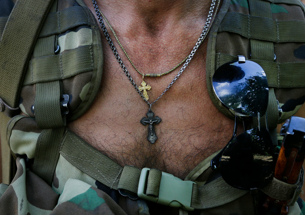 . An Orthodox church crosses hangs on a chest of a pro-Russian rebel in the town of Novoazovsk, in eastern Ukraine, Friday, Aug. 29, 2014. In Novoazovsk, pro Russian rebel fighters looked to be in firm control, well-equipped and relaxed. At least half a dozen tanks were seen on roads around the town, although the total number at the rebels\' disposal is believed to be much greater. Novoazovsk fell swiftly to the rebels Wednesday after being pounded by shelling. (AP Photo/Sergei Grits)