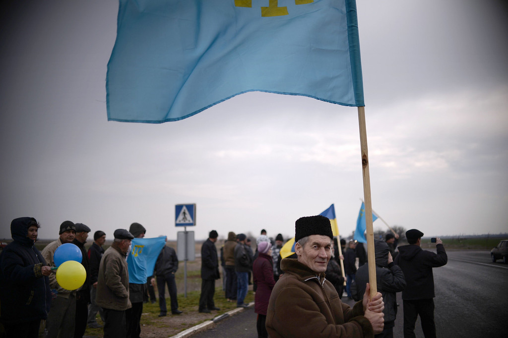 . A Crimean Tatar waves a Tatar flag during a pro-Ukrainian demonstration near the village of Ilinka on March 14, 2014, two days before a referendum in Crimea over its bid to break away from Ukraine and join Russia. The pro-Moscow leader of Ukraine\'s flashpoint Crimea peninsula called today on Russian-speaking eastern regions of Ukraine to hold their own referendums on switching over to Kremlin rule. DIMITAR DILKOFF/AFP/Getty Images