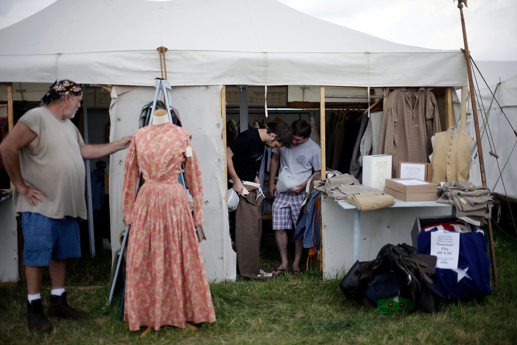 . Shoppers view goods in one of the many tents selling items including boots made in them Civil War era manner and souvenirs at Bushey Farm during ongoing activities commemorating the 150th anniversary of the Battle of Gettysburg, Thursday, June 27, 2013, in Gettysburg, Pa. (AP Photo/Matt Rourke)