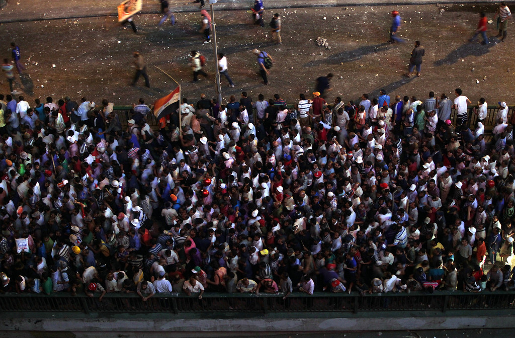 . Supporters of Egypt\'s Islamist President Mohammed Morsi mass on a bridge during clashes with Morsi opponents near Maspero, where Egypt\'s state tv and radio station is located, in Cairo, Egypt, Friday, July 5, 2013. Tens of thousands of Islamists streamed across a Nile River bridge toward Cairoís Tahrir Square on Friday, threatening a showdown moments after the top leader of the Muslim Brotherhood defiantly spoke before a cheering crowd of supporters, vowing to reinstate ousted President Mohammed Morsi and end military rule. (AP Photo/Khalil Hamra)