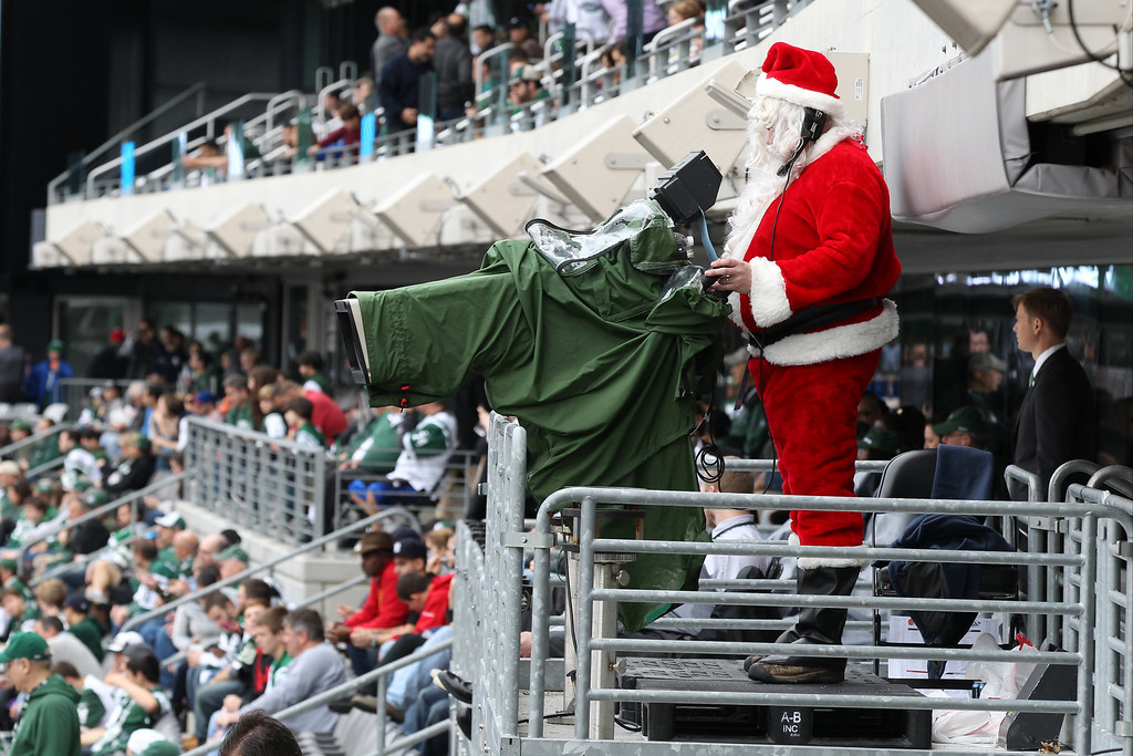 . Eric Brush operates a video camera during the first half of an NFL football game between the New York Jets and the Cleveland Browns, Sunday, Dec. 22, 2013, in East Rutherford, N.J.  (AP Photo/Peter Morgan)