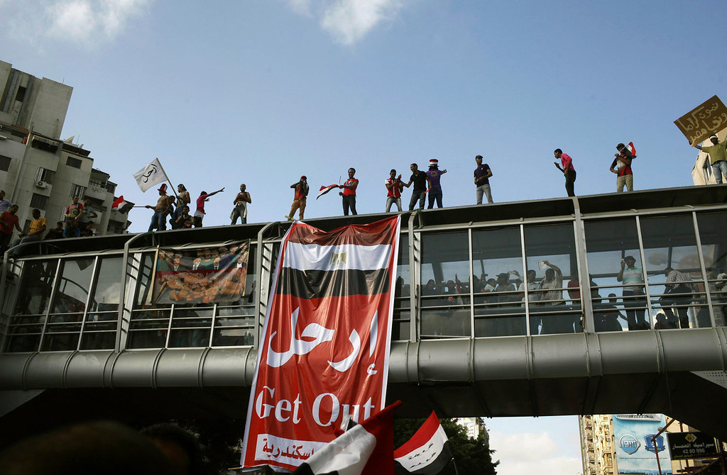". Anti-Mursi protesters chant slogans on a pedestrian bridge with a banner that reads ""Get Out\"", during a massive protest in Alexandria June 30, 2013. Egyptians poured onto the streets on Sunday, swelling crowds that opposition leaders hope will number into the millions by evening and persuade Islamist President Mohamed Mursi to resign. REUTERS/Asmaa Waguih"