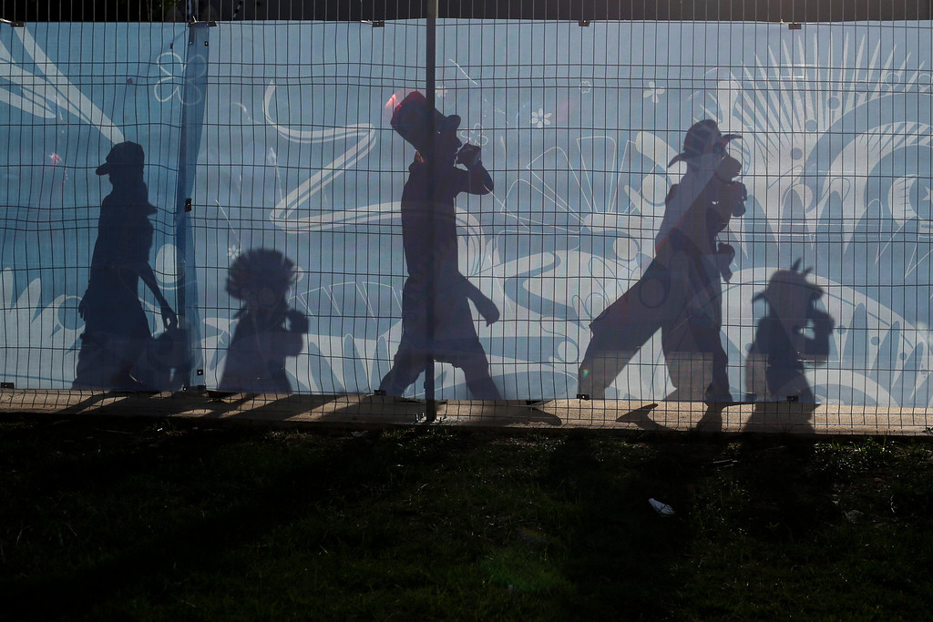 . The shadows of Chile soccer fans are cast on a fence outside the Arena Pantanal as they arrive to their team\'s World Cup match with Australia in Cuiaba, Brazil, Friday, June 13, 2014. (AP Photo/Felipe Dana)