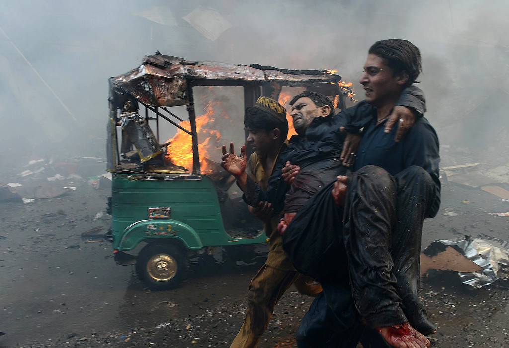 . Pakistani men carry an injured blast victim at the site of a bomb explosion in the busy Kissa Khwani market in Peshawar on September 29, 2013. The bomb explosion killed at least 31 people.  HASHAM AHMED/AFP/Getty Images